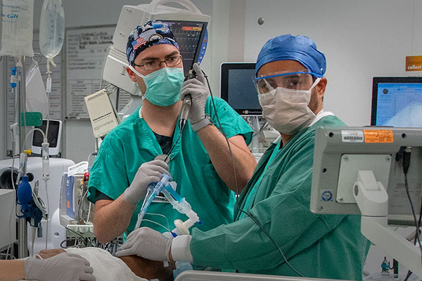 Two anesthesiolgists monitoring the vitals of an emergency room patient as they administer an analgesic for a patient with a fractured bone