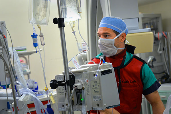 A resident anesthesiologist monitoring the vitals of an anesthetized patient